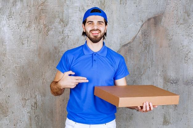 Männlicher kurier in blauer uniform mit einer pappschachtel zum mitnehmen