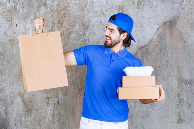 Männlicher kurier in blauer uniform mit papppaketen, einer einkaufstasche und einer plastikbox zum mitnehmen