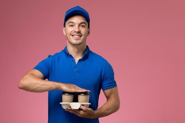Männlicher kurier in der blauen uniform, die kaffeetassen hält, die auf rosa, einheitliche dienstauftragszustellung lächeln
