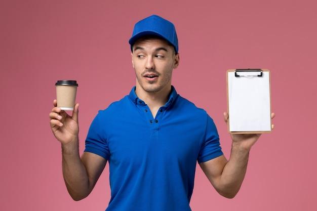 Männlicher kurier in der blauen uniform, die kaffeetassen-notizblock auf rosa, arbeiteruniform-dienstlieferung hält