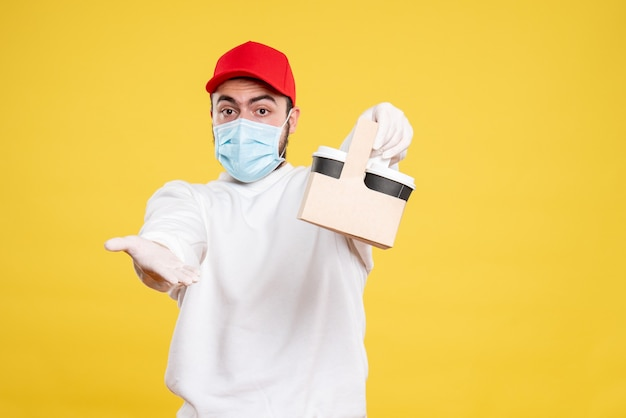 Männlicher kurier in maske hält lieferkaffee auf gelb