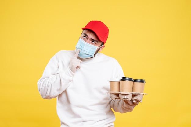 Männlicher kurier in maske mit kaffee auf gelb
