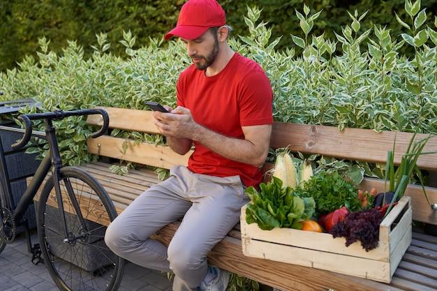 Männlicher kurier in uniform, der draußen auf der bank sitzt und benutzt