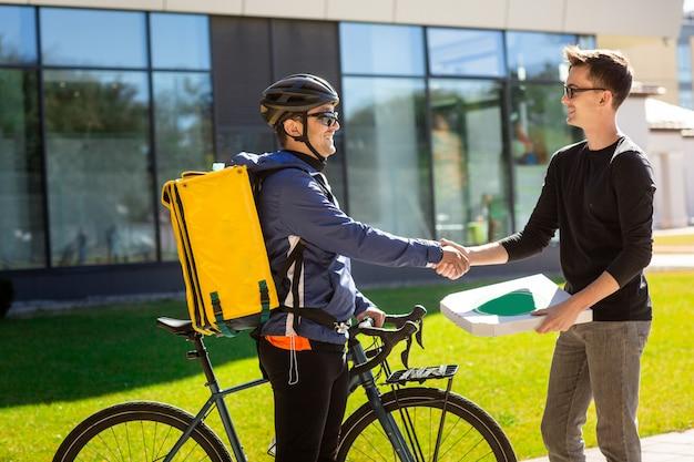 Männlicher kurier mit dem fahrrad und thermischer tasche, die dem kunden auf straße nahe dem büro einen kasten geben.