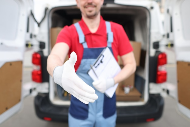 Männlicher kurier mit dokumenten, die dem kunden die hand für die handshake-nahaufnahme geben