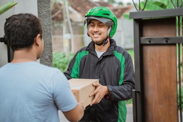 Männlicher kurier mit helm, der paket zum kunden liefert
