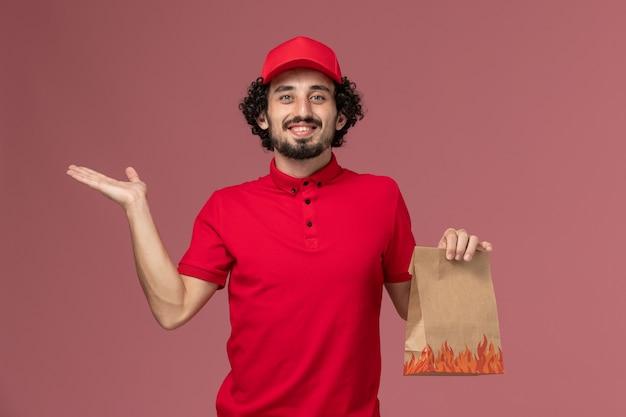 Männlicher kurierlieferant der vorderansicht im roten hemd und im umhang, der lebensmittelpaket auf rosa wandarbeitsdienstlieferdienstmitarbeiter hält