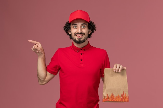 Männlicher kurierlieferant der vorderansicht im roten hemd und im umhang, der lebensmittelpaket auf rosa wanddienstlieferungsjobarbeitsarbeitsangestellter hält
