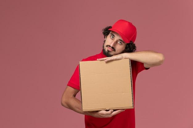 Männlicher kurierlieferant der vorderansicht im roten hemd und im umhang, der lieferung-nahrungsmittelbox auf dem rosa schreibtischdienst-lieferfirmenmitarbeiter hält