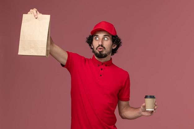 Männlicher kurierlieferant der vorderansicht im roten hemd und im umhang, die braune kaffeetasse und lebensmittelpaket auf hellrosa wanddienstmitarbeiter-arbeiter halten