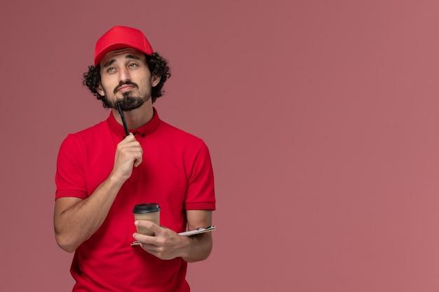 Männlicher kurierlieferant der vorderansicht im roten hemd und im umhang, die braune kaffeetasse und notizblock mit stift denken, der auf hellrosa wanddienstlieferungsmitarbeiterjob denkt