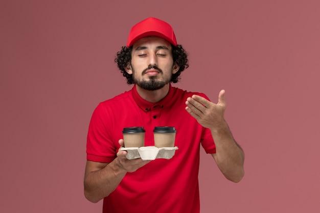 Männlicher kurierlieferant der vorderansicht im roten hemd und im umhang, die braune kaffeetassen der lieferung halten, die auf rosa wanddienstmitarbeiter riechen