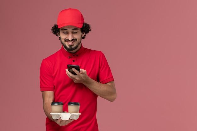 Männlicher kurierlieferant der vorderansicht im roten hemd und im umhang, die braune kaffeetassen der lieferung halten und foto auf hellrosa wanddienstlieferungsmitarbeiter machen