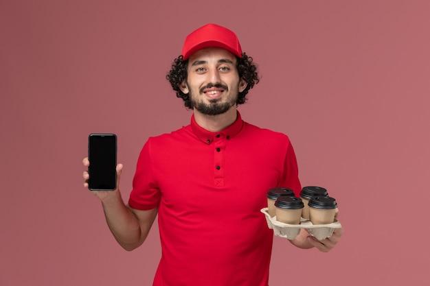 Männlicher kurierlieferant der vorderansicht im roten hemd und im umhang, die braune kaffeetassen der lieferung mit telefon auf dem rosa wanddienstmitarbeiter halten