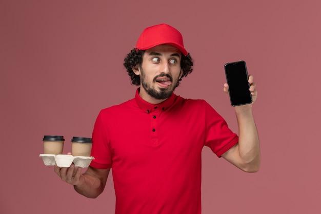 Männlicher kurierlieferant der vorderansicht im roten hemd und im umhang, die braune kaffeetassen und telefon der lieferung auf dem hellrosa wanddienstmitarbeiter-mitarbeiter halten