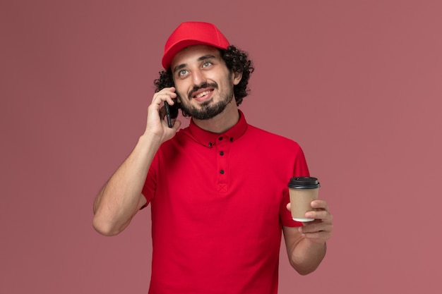Männlicher kurierlieferant der vorderansicht im roten hemd und im umhang, die braune lieferkaffeetasse halten und am telefon auf hellrosa wanddienstlieferungsmitarbeiterarbeit sprechen
