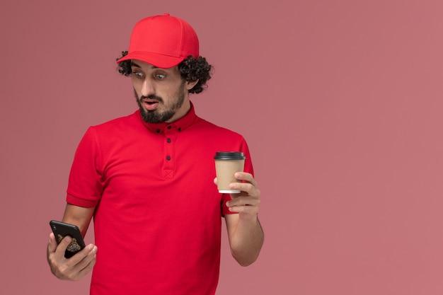 Männlicher kurierlieferant der vorderansicht im roten hemd und im umhang, die braune lieferkaffeetasse halten und telefon auf hellrosa wanddienstlieferungsmitarbeiter verwenden