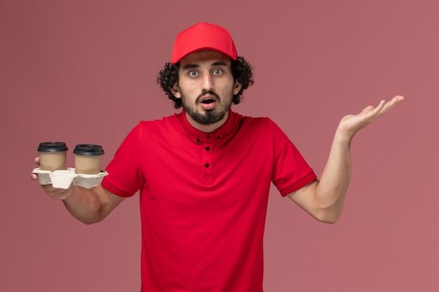 Männlicher kurierlieferant der vorderansicht im roten hemd und im umhang, die braune lieferkaffeetassen auf hellrosa wanddienstlieferungsmitarbeiterjob halten