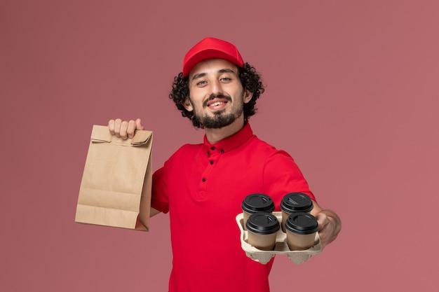 Männlicher kurierlieferant der vorderansicht im roten hemd und im umhang, die braune lieferkaffeetassen mit lebensmittelpaket auf rosa wandarbeitsdienstlieferungsmitarbeiter halten