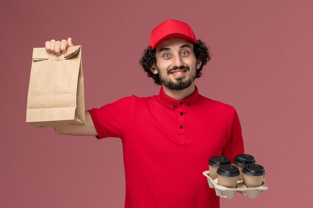 Männlicher kurierlieferant der vorderansicht im roten hemd und im umhang, die braune lieferkaffeetassen mit lebensmittelpaket auf rosa wanddienstlieferungsmitarbeiter männlich halten