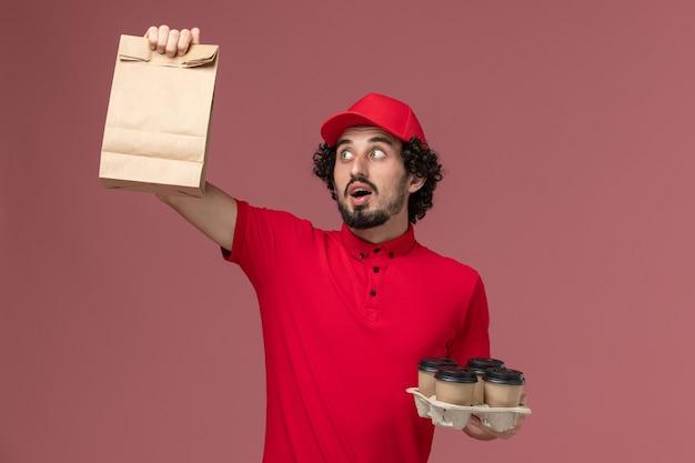 Männlicher kurierlieferant der vorderansicht im roten hemd und im umhang, die braune lieferkaffeetassen mit lebensmittelpaket auf rosa wanddienstlieferungsmitarbeiterarbeit halten