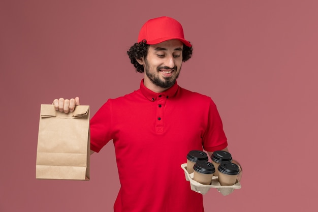 Männlicher kurierlieferant der vorderansicht im roten hemd und im umhang, die braune lieferkaffeetassen mit lebensmittelpaket auf rosa wanddienstlieferungsmitarbeiterjob halten