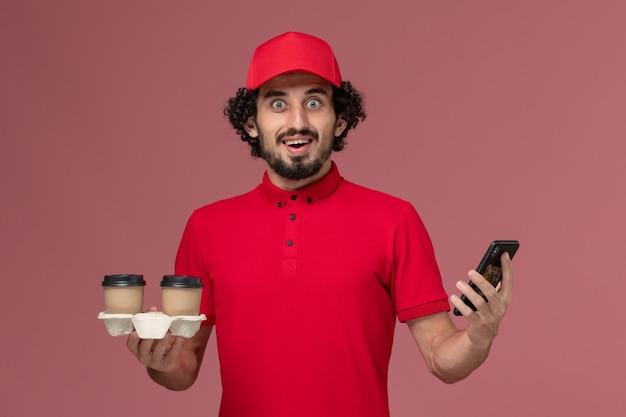 Männlicher kurierlieferant der vorderansicht im roten hemd und im umhang, die braune lieferkaffeetassen und telefon auf hellrosa wanddienstlieferungsmitarbeiter-arbeiterjob halten