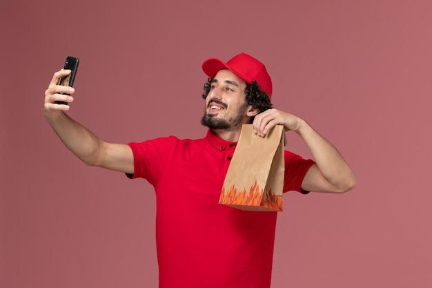 Männlicher kurierlieferant der vorderansicht im roten hemd und im umhang, die foto mit lebensmittelpaket auf rosa wanddienstlieferungsmitarbeiter nehmen