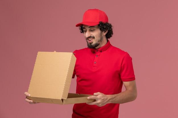 Männlicher kurierlieferant der vorderansicht im roten hemd und im umhang, die nahrungsmittelbox auf dem rosa wanddienstlieferungsmitarbeiter halten