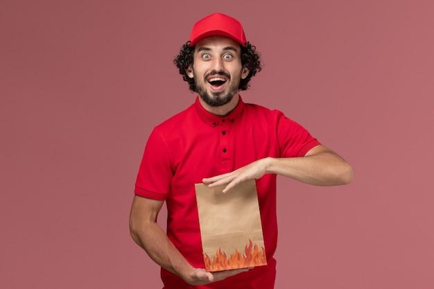 Männlicher kurierlieferant der vorderansicht im roten hemd und im umhang, die papiernahrungsmittelpaket auf rosa wanddienstlieferungsmitarbeiterarbeit halten