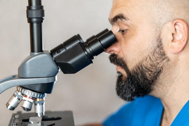 Männlicher laborassistent, der biomaterialproben in einem mikroskop untersucht