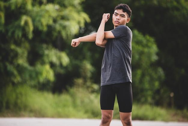 Männlicher läufer, der die übung ausdehnend tut und bereiten sich für training vor