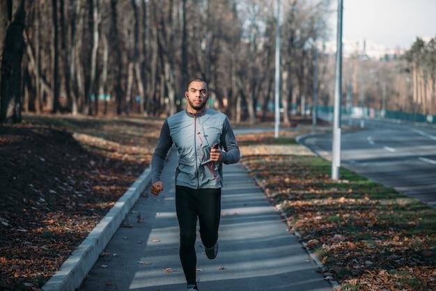 Männlicher läufer in sportbekleidung beim training im freien. jogger beim morgendlichen training. athletischer mann, der marathon läuft