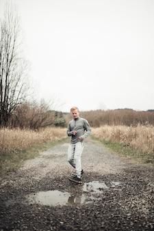 Männlicher läuferhalt nahe der pfütze beim laufen auf schotterweg auf dem gebiet