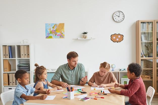 Männlicher lehrer, der mit einer multiethnischen gruppe von kindern arbeitet, die bilder während des kunstunterrichts in der schule oder im entwicklungszentrum zeichnen