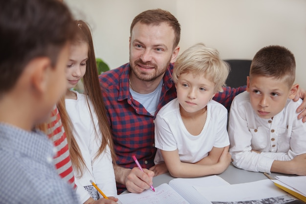 Männlicher lehrer, der mit kindern an der vorschule arbeitet