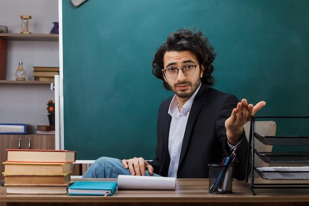 Männlicher lehrer mit brille sitzt am tisch mit schulwerkzeugen im klassenzimmer