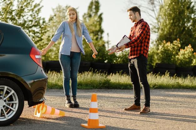 Männlicher lehrer und frau am auto und abgestürzter kegel, unterricht in der fahrschule. mann, der dame beibringt, fahrzeug zu fahren. führerscheinausbildung