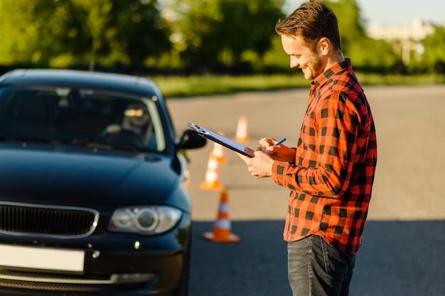 Männlicher lehrer und frau im auto, leitkegel, unterricht in der fahrschule. mann, der dame beibringt, fahrzeug zu fahren. führerscheinausbildung