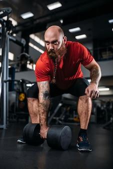 Männlicher lifter, der übung mit hanteln im fitnessstudio tut