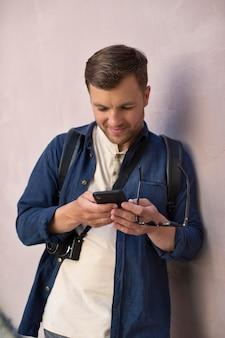 Männlicher lokaler reisender, der sein telefon überprüft