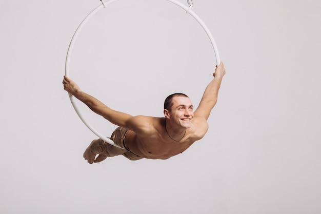 Männlicher luftturner führt akrobatisches element im ring durch