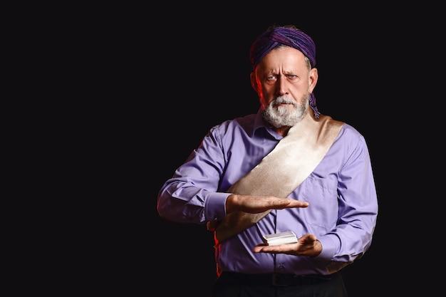 Männlicher magier mit karten auf dunkler oberfläche