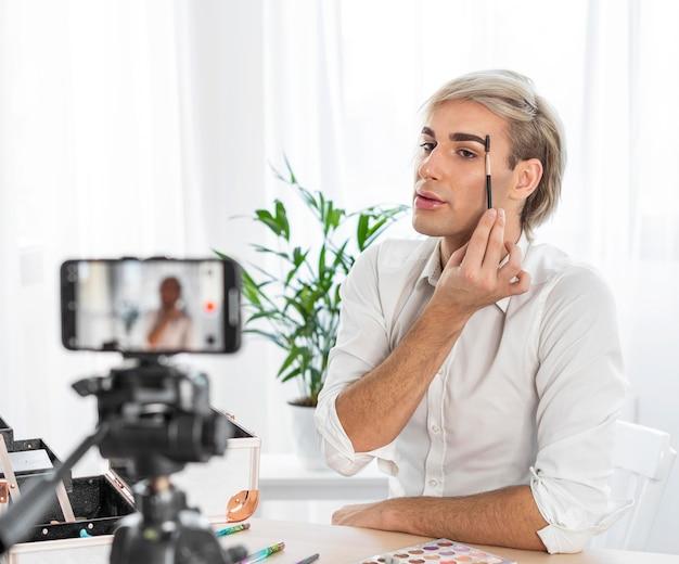 Männlicher make-up-blick, der ein video mit handy macht