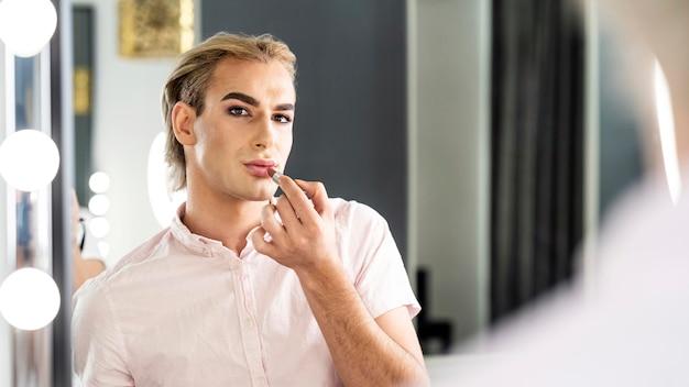 Männlicher make-up-blick, der in den spiegel schaut