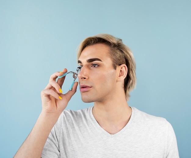 Männlicher make-up-look mit einem wimpernzange