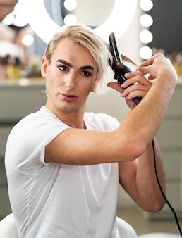 Männlicher make-up-look und verwendung eines bügeleisens