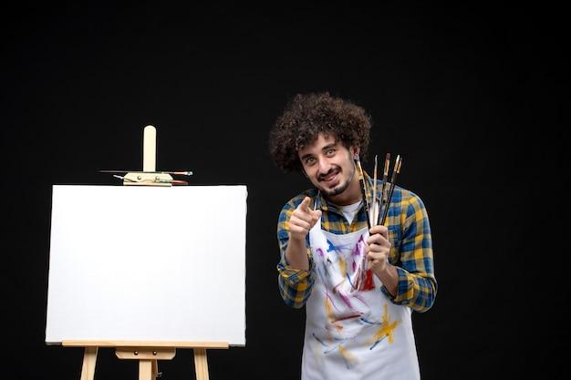 Männlicher maler der vorderansicht, der quasten zum zeichnen auf dunkler wand hält