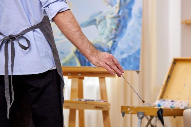Männlicher maler in der schürze, die meisterwerk mit pinsel auf leinwand macht, bild auf staffelei. design, kunst, handwerk, malerei konzept