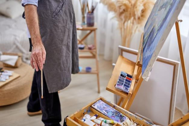 Männlicher maler mann in der schürze während des arbeitsprozesses, männlich unter verwendung von pinseln, verschiedene materialien malt werkzeuge zum malen